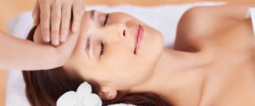 Beautiful fresh woman having facial massage in spa centre